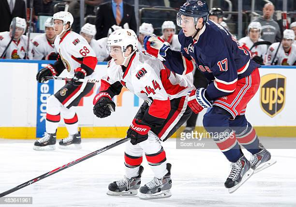 John Moore of the New York Rangers jumps past JeanGabriel Pageau of the Ottawa Senators at Madison Square Garden on April 05 2014 in New York City...