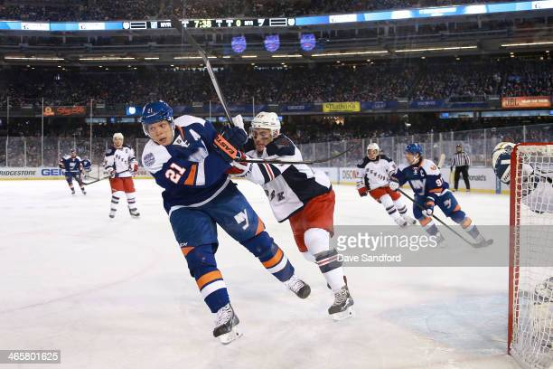 John Moore of the New York Rangers pushes at Kyle Okposo of the New York Islanders in the first period during the 2014 Coors Light NHL Stadium Series...