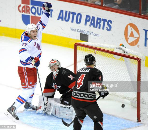 John Moore of the New York Rangers react after scoring a goal against Anton Khudobin and Andrej Sekera of the Carolina Hurricanes during the third...