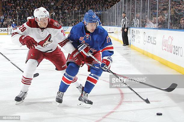 John Moore of the New York Rangers skates with the puck against Michael Stone of the Arizona Coyotes at Madison Square Garden on February 26 2015 in...