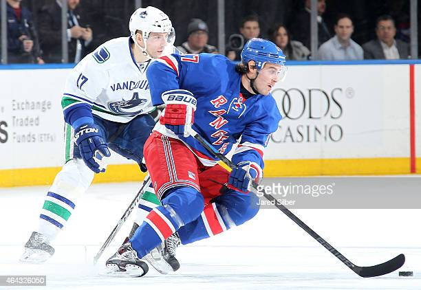 John Moore of the New York Rangers skates with the puck against Radim Vrbata of the Vancouver Canucks at Madison Square Garden on February 19 2015 in...