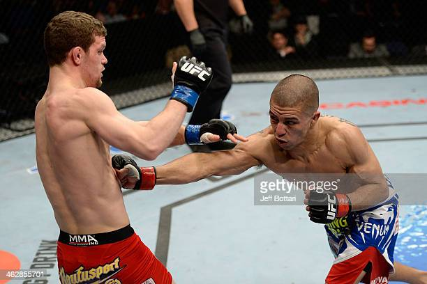 John Moraga punches Dustin Ortiz in their flyweight fight during the UFC Fight Night event inside The Arena at Gwinnett Center on January 15, 2014 in...