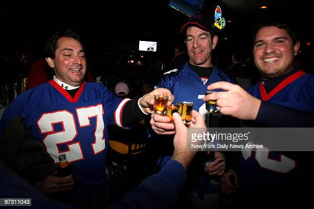 John Morro of Hasbrouck Heights NJ Dave Ern of Middletown NJ and Jeff Morro of Hasbrouck Heights NJ toast their team as they and other Giiants fans...