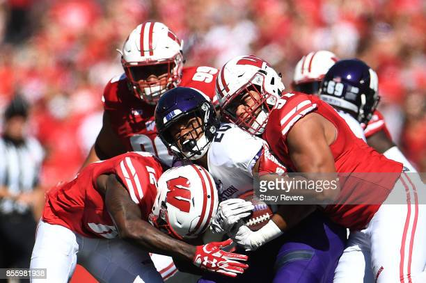 John Moten IV of the Northwestern Wildcats is brought down by Alec James and Natrell Jamerson of the Wisconsin Badgers during the third quarter of a...