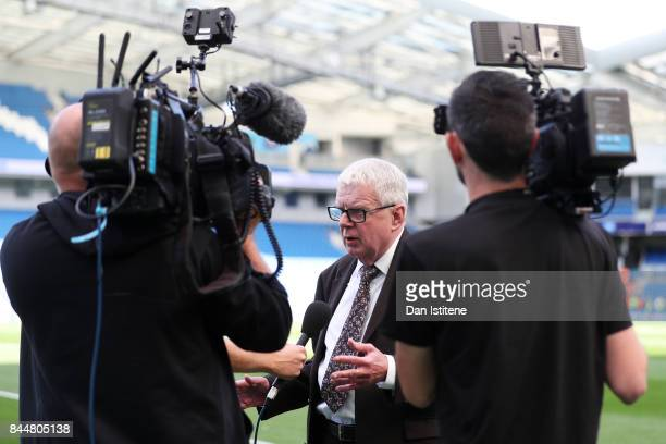 John Motson presents pitchside prior to the Premier League match between Brighton and Hove Albion and West Bromwich Albion at Amex Stadium on...