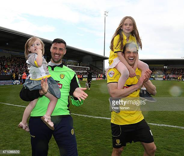 John Mousinho and Scott Shearer of Burton Albion celebrate with their daughterson a lap of honour at the end of the Sky Bet League Two match between...