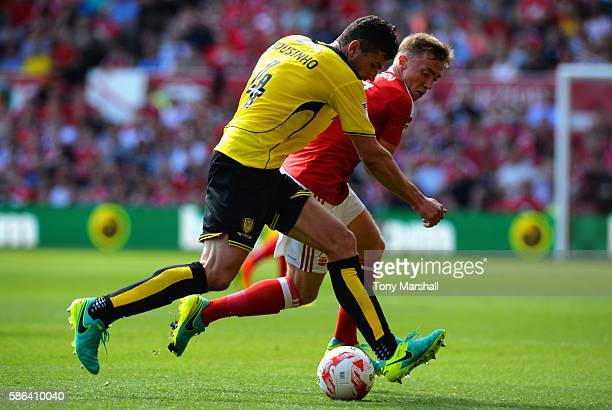 John Mousinho of Burton Albion is tackled by Ben Osborn of Nottingham Forest during the Sky Bet Championship match between Nottingham Forest and...