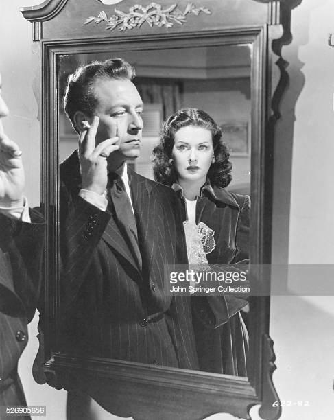 John Muller aka Dr Victor Emil Bartok touches the scar on his cheek as Evelyn Hahn watches in the 1948 film noir Hollow Triumph