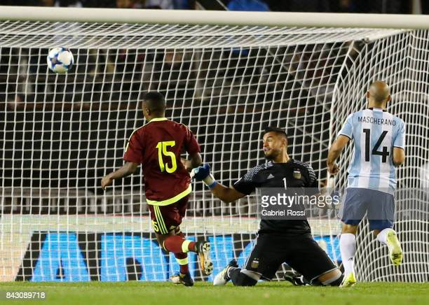 John Murillo of Venezuela kicks the ball to score the first goal of his team past Sergio Romero goalkeeper of Argentina during a match between...