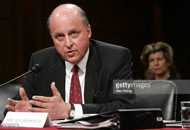 John Negroponte testifies as his wife Diana looks on during a Senate Select Intelligence Committee hearing on Capitol Hill April 12, 2005 in...