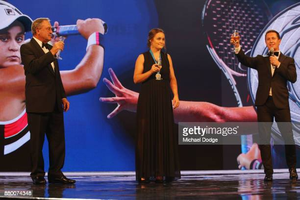 John Newcombe medallist Ashleigh Barty is toasted on the podium with John Newcombe and host Rove McManus at the 2017 Newcombe Medal at Crown...