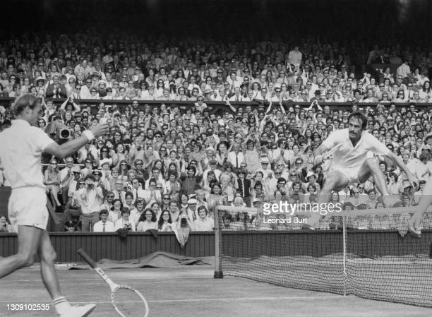 John Newcombe of Australia jumps over the net after defeating Stan Smith of the United States in their Men's Singles Final match on Centre Court at...