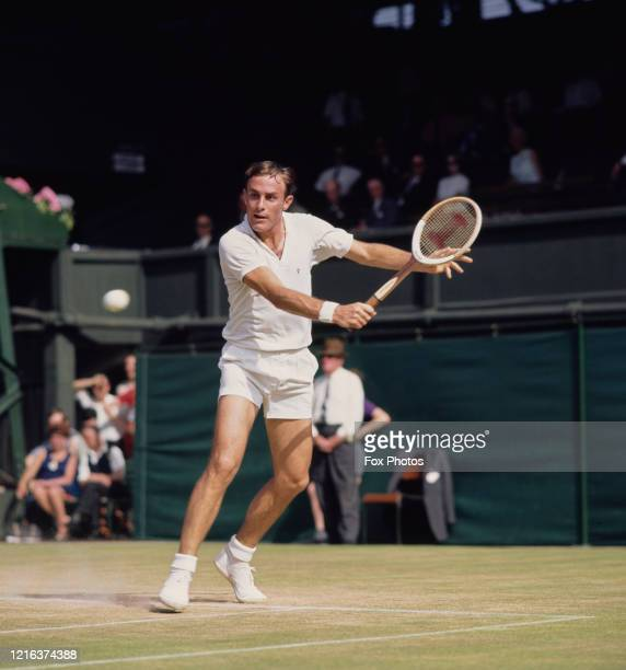 John Newcombe of Australia makes a backhand return against Arthur Ashe during their Men's Singles fourth round match at the Wimbledon Lawn Tennis...