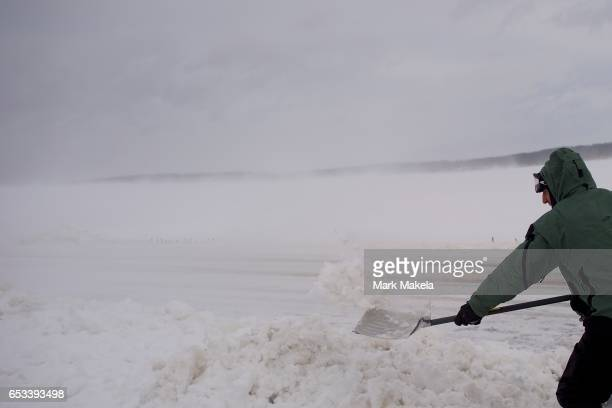 John Noyes shovels snow during a windstorm after a snowfall March 14 2017 in Ephrata Pennsylvania A blizzard is forecast to bring more than a foot of...