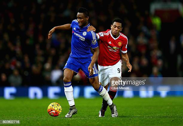 John Obi Mikel of Chelsea holds off a challenge from Anthony Martial of Manchester United during the Barclays Premier League match between Manchester...