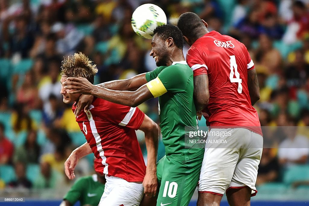 John Obi Mikel (C) of Nigeria heads for the ball with Andreas Maxso (L) and Edigerson Gomes (R) of Denmark during the Rio 2016 Olympic Games mens quarter-final football match Nigeria vs Denmark, at the Arena Fonte Nova Stadium in Salvador, Brazil on August 13, 2016. / AFP / NELSON