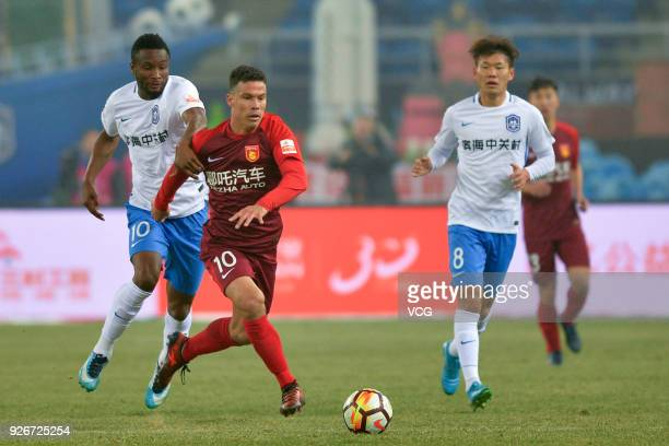John Obi Mikel of Tianjin Teda and Hernanes of Hebei China Fortune compete for the ball during the 2018 Chinese Football Association Super League...