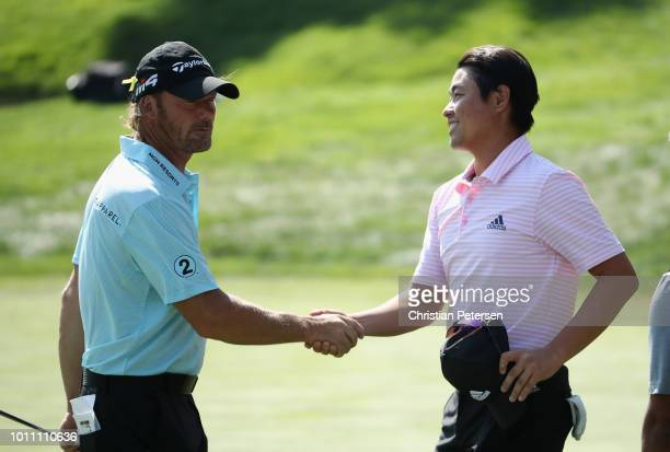 John Oda shakes hands with Alex Cejka of Germany on the 18th green following the third round of the Barracuda Championship at Montreux Country Club...