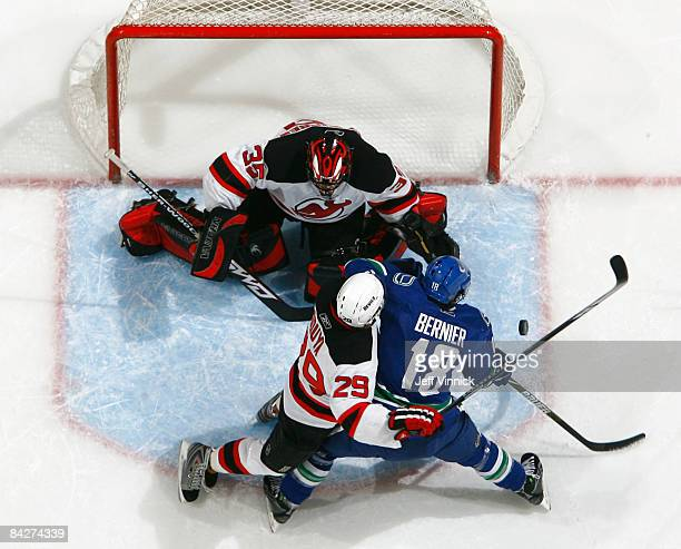 John Oduya of the New Jersey Devils and Steve Bernier of the Vancouver Canucks battle for the rebound after Scott Clemmensen of the New Jersey Devils...