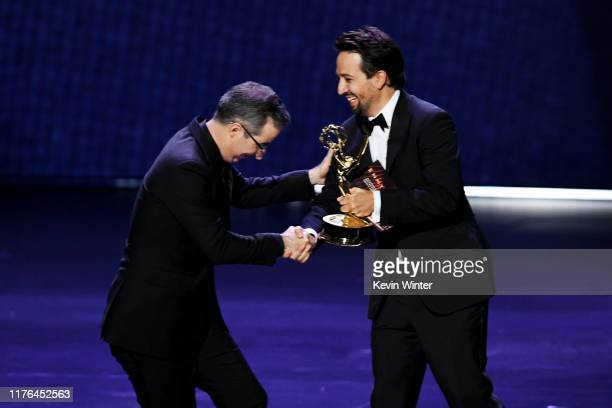 John Oliver accepts the Outstanding Writing for a Variety Series award for 'Last Week Tonight with John Oliver' from LinManuel Miranda onstage during...