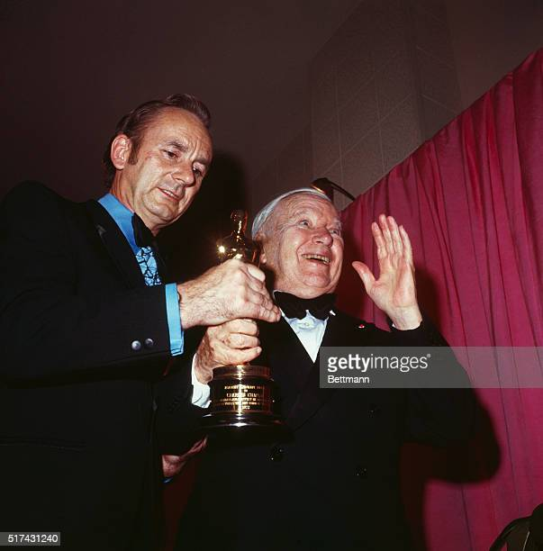 John Ormond admires the special Oscar Charlie Chaplin won in the 44th annual Academy Awards ceremony while an elated Chaplin acknowledges his fans