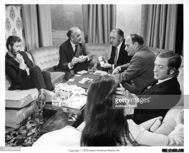 John Osborne playing cards with other men as Geraldine Moffat and Michael Caine chat in a scene from the film 'Get Carter' 1971