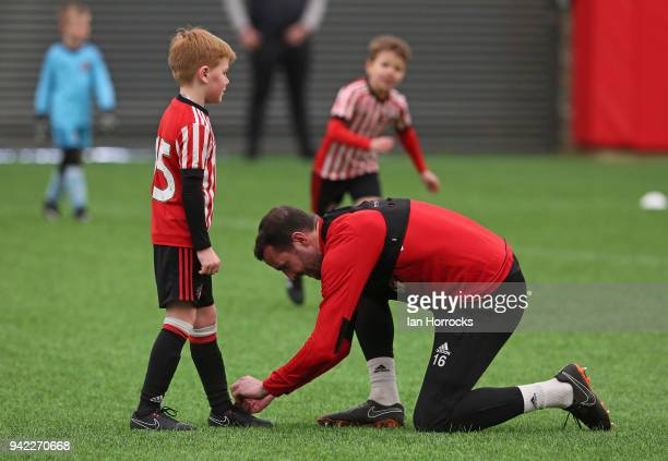 John O'Shea helps a under 9 players with his laces during a training session between the First Team and the under 9's at The Academy of Light on...