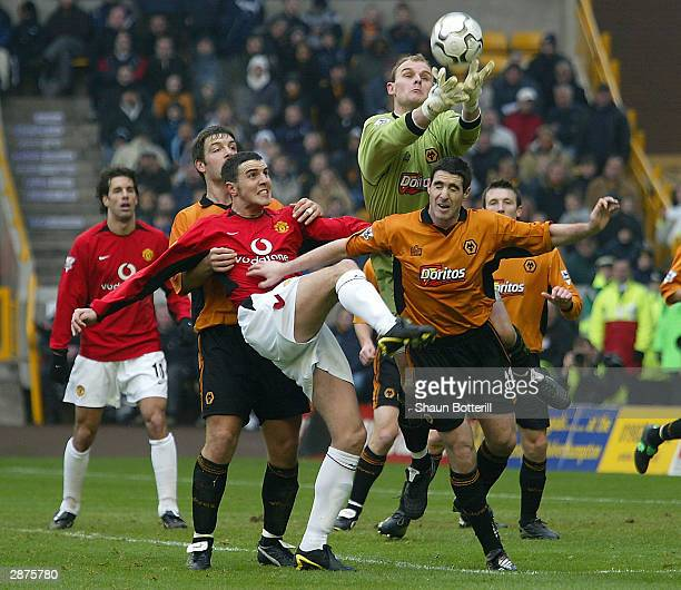 John O'Shea of Manchester United battles for the ball in the air with goalkeeper Michael Howard and Mark Kennedy of Wolverhampton Wanderers during...