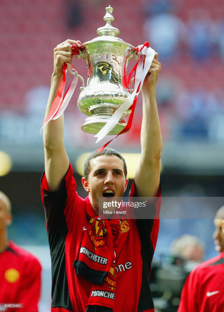 John O'Shea of Manchester United celebrates with the trophy following victory in the 123rd FA Cup Final between Manchester United and Millwall held at The Millennium Stadium on May 22, 2004 in Cardiff, Wales.