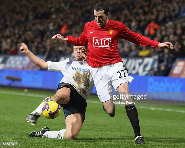 John O'Shea of Manchester United clashes with Kevin Davies of Bolton Wanderers during the Barclays Premier League match between Bolton Wanderers and...