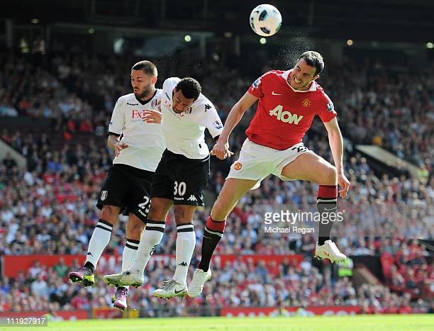 John O'Shea of Manchester United wins a header against Moussa Dembele and Clint Dempsey of Fulham during the Barclays Premier League match between...
