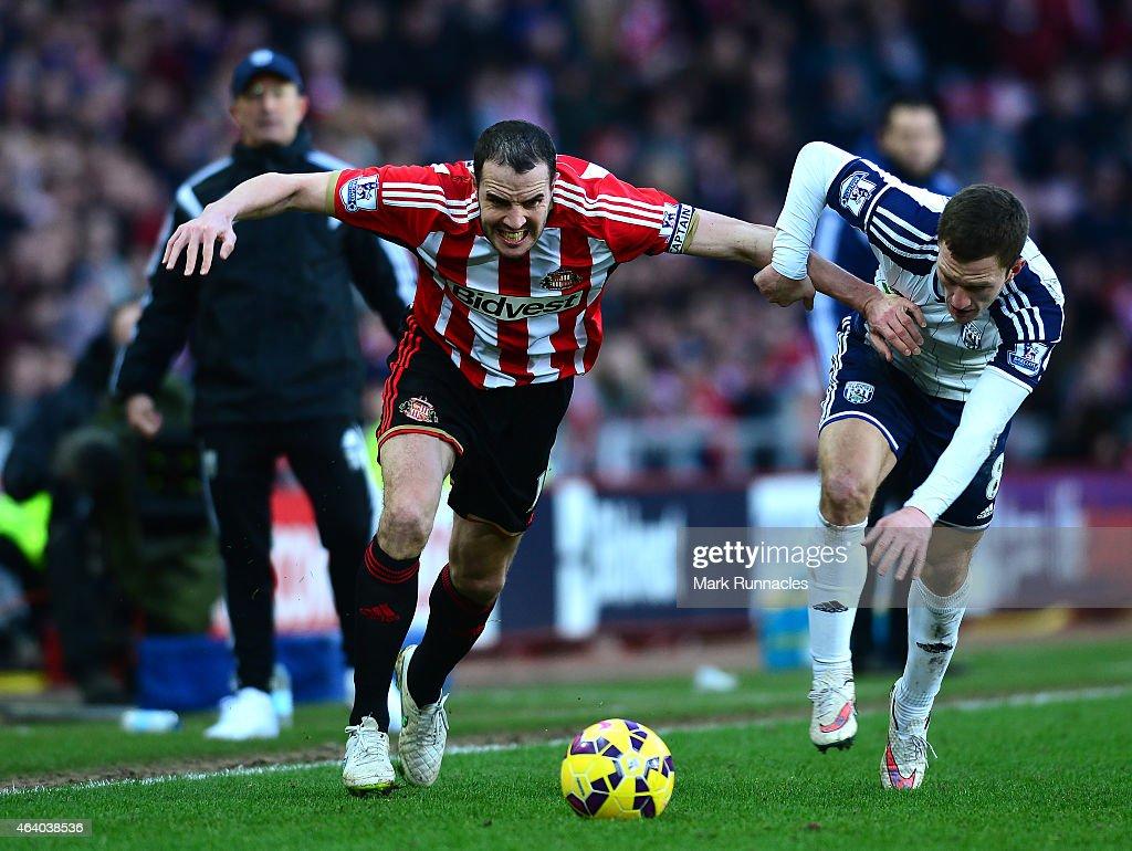 John O'Shea of Sunderland and Craig Gardener of West Bromwich Albion tangle during the Barclays Premier League match between Sunderland and West Bromwich Albion at Stadium of Light on February 21, 2015 in Sunderland, England.