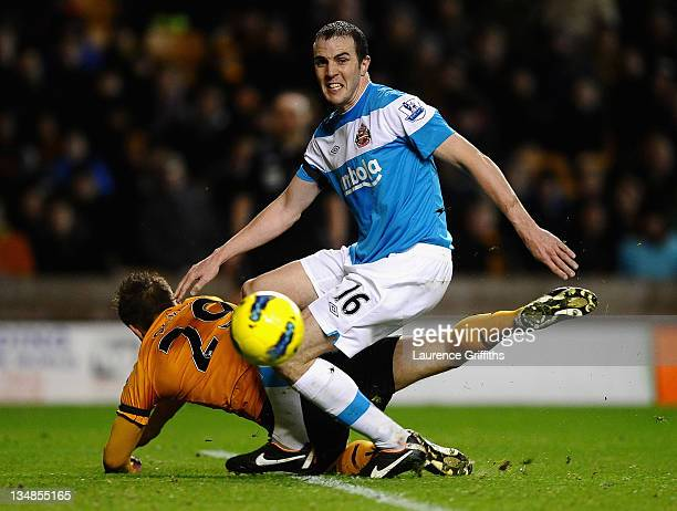 John O'Shea of Sunderland battles with Kevin Doyle of Wolverhampton Wanderers during the Barclays Premier League match between Wolverhampton...