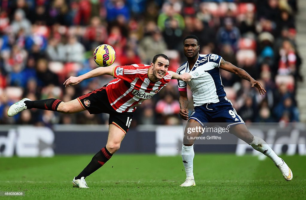 John O'Shea of Sunderland heads the ball clear under pressure from Brown Ideye of West Brom during the Barclays Premier League match between Sunderland and West Bromwich Albion at Stadium of Light on February 21, 2015 in Sunderland, England.