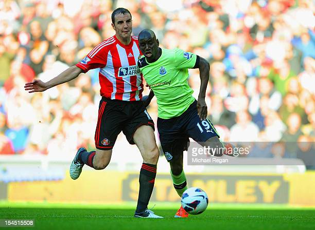John O'Shea of Sunderland in action with Demba Ba of Newcastle during the Barclays Premier League match between Sunderland and Newcastle United at...