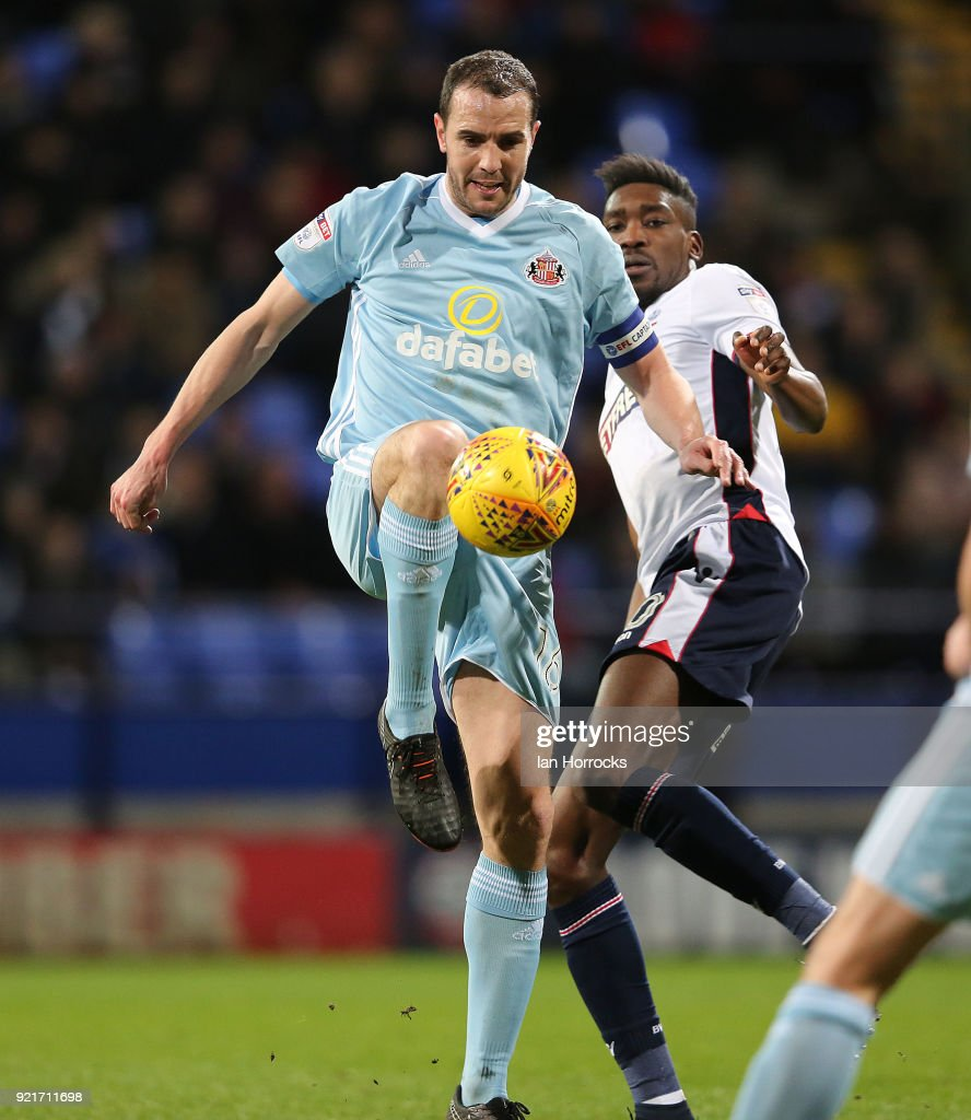 John O'Shea of Sunderland (R) is challenged by Sammy Ameobi during the Sky Bet Championship match between Bolton Wanderers and Sunderland at Macron Stadium on February 20, 2018 in Bolton, England.
