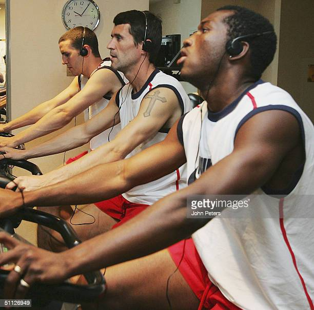 John O'Shea, Roy Keane and Eric Djemba-Djemba of Manchester United on exercise bikes during a gym session during their 2004 USA Tour, which is taking...