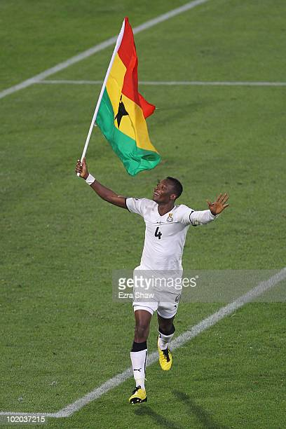 John Pantsil of Ghana celebrates their victory running with the flag after the 2010 FIFA World Cup South Africa Group D match between Serbia and...