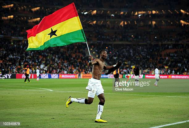 John Pantsil of Ghana celebrates with a national flag having qualified for the next round despite losing the match during the 2010 FIFA World Cup...
