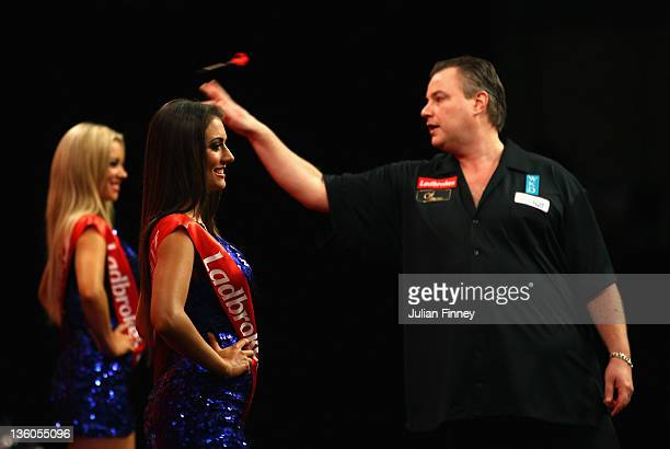 John Part of Canada throws as the oche girls looks on before his match against John Henderson of Scotland during day seven of the 2012 Ladbrokescom...