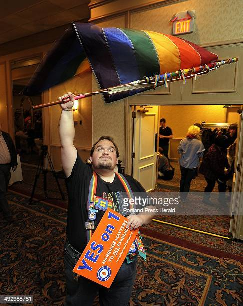 John Paschal of Sanford waves a flag while waiting for election results at the Mainers United for Marriage campaign party at the Holiday Inn by the...
