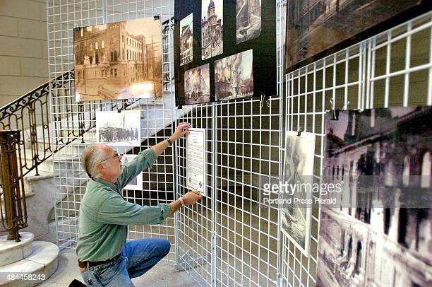 John Patriquin/Staff Photographer Wed January 23 2008 Senior city hall printer Gary Goddard hangs a collection of photos and images of the 1908...
