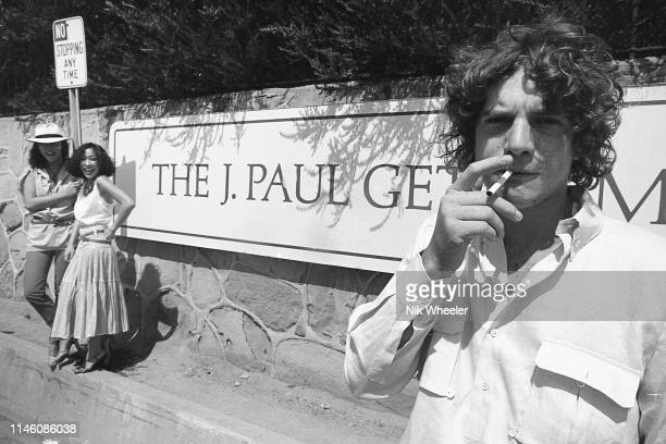 John Paul Getty III grandson of billionaire Paul Getty stands with two friends in front of entrance to the Getty Villa Museum in Santa Monica circa...