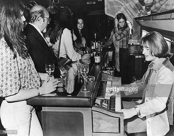 John Paul Jones of English rock group Led Zeppelin plays a Thomas electric organ behind the bar on board a private Boeing 720B airliner known as 'The...