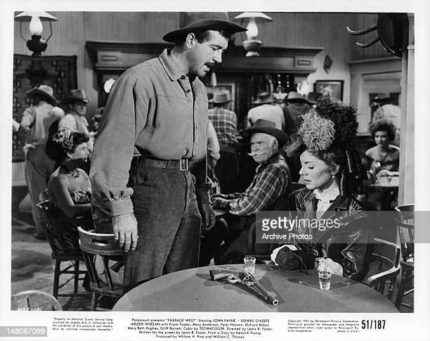 John Payne looking at gun on Arleen Whelan's table in a scene from the film 'Passage West' 1951