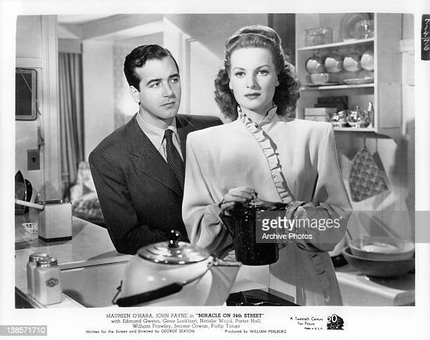 John Payne stands in back of Maureen O'Hara as she holds a coffee pot in a scene from the film 'Miracle On 34th Street' 1947