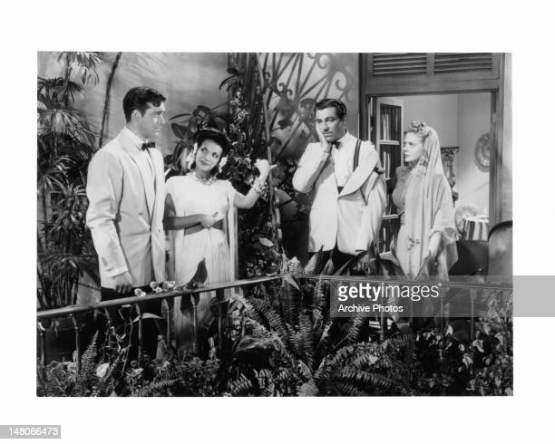 John Payne stares at Alice Faye as they stand with Carmen Miranda and a man holding his hand against his cheek in a scene from the film 'WeekEnd In...