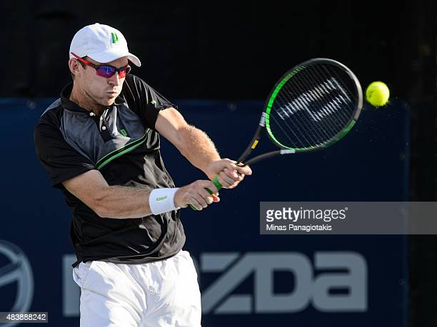 John Peers of Australia hits a return against Leander Paes of India and Andy Murray of Great Britain during day four of the Rogers Cup at Uniprix...