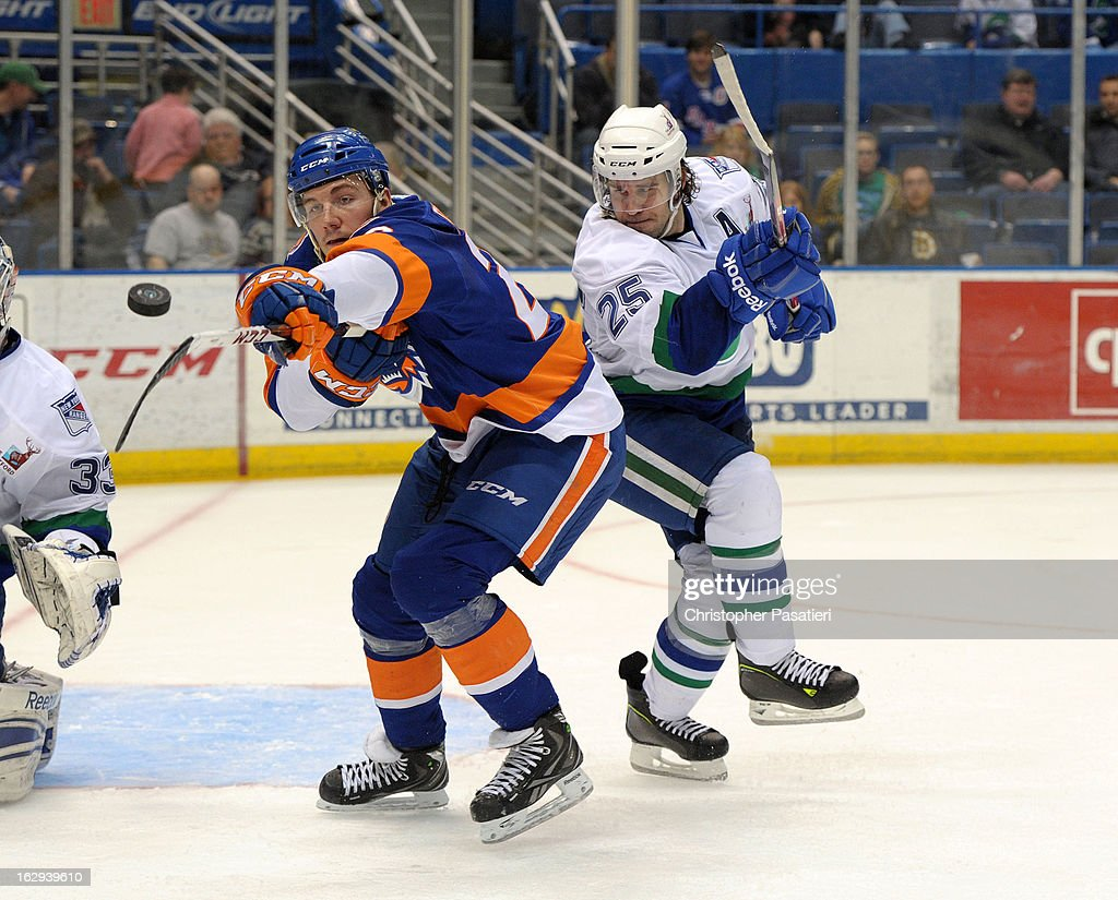 John Persson #23 of the Bridgeport Sound Tigers reaches for the puck against Sean Collins #25 of the Connecticut Whale during an American Hockey League game on March 1, 2013 at the XL Center in Hartford, Connecticut.