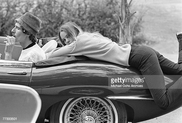 John Phillips and Michelle Phillips of the rock group 'The Mamas The Papas' pose for a picture on a Jaguar EType car as John tokes from a hashish...